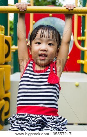 Asian Kid Hanging On Bar