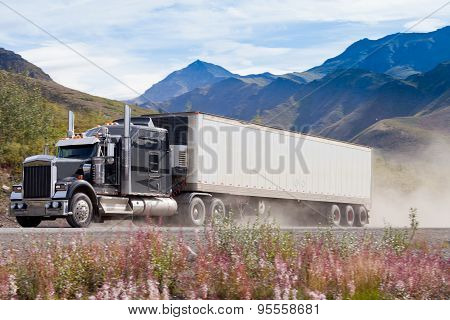 Semi Truck On Dusty Road In Mountain Landscape