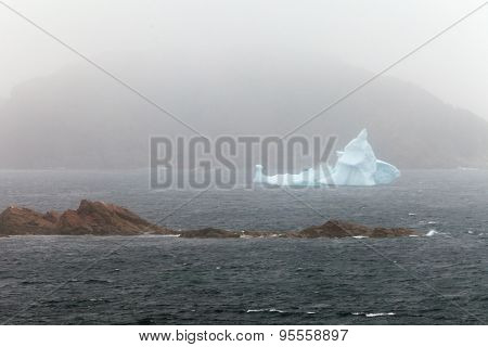 Iceberg Melts Near Rocky Shore Hidden In Misty Fog