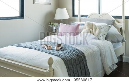 White Bedroom With Pillows And Doll On White Bed