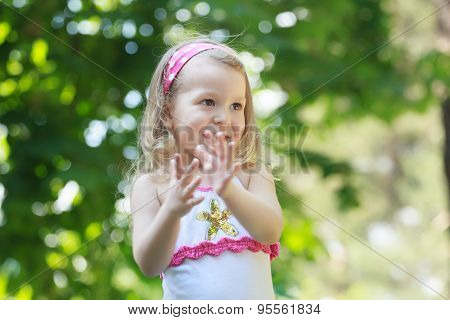 Laughing blonde toddler girl clapping with her palms