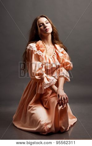 Studio full length portrait of a pretty woman in pink sitting