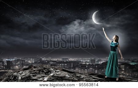 Young attractive woman in green dress reaching moon
