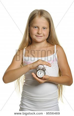 The Girl Holds An Alarm Clock In Hands