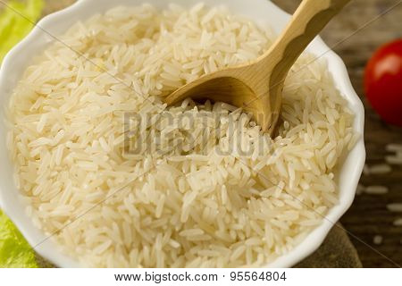 White Plate Of Long Grain Rice With A Spoon, Cherry Tomato, Green Lettuce On Wooden Background