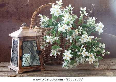 Bouquet From Jasmin Branches In A Wattled Basket And An Old Lantern