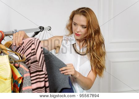 Girl Chooses Clothes In Clothes Shop