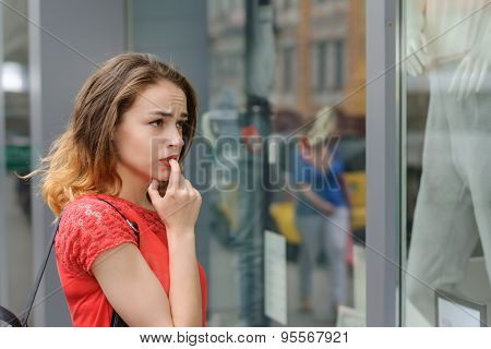 Girl In A Red Blouse Standing Near Storefront Pensively