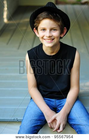 Happy smiling stylish boy in a black hat