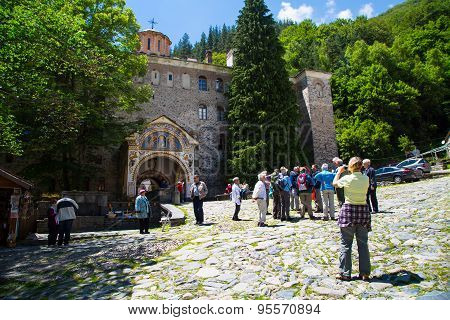 Tourists Near The Entrance Arch Of Famous Rila Monastery, Bulgaria
