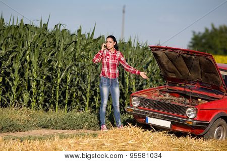 Girl On The Phone Beside Broken Car