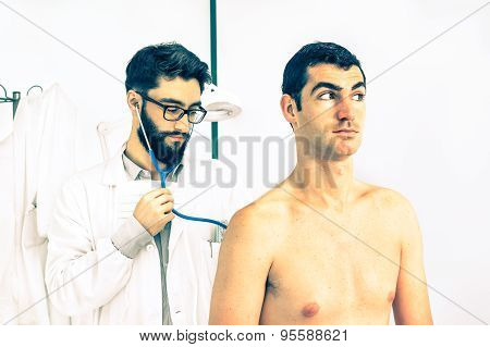 Young Hipster Primary Doctor At Work Auscultating Male Patient In Private Clinic