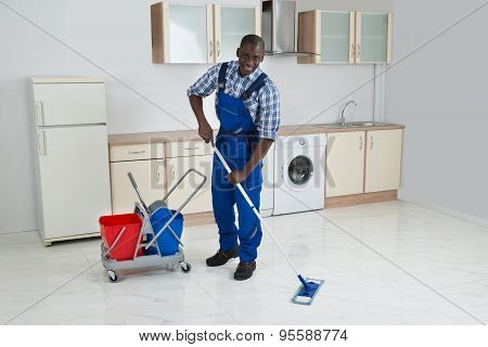 African Male Worker Cleaning Floor With Mop