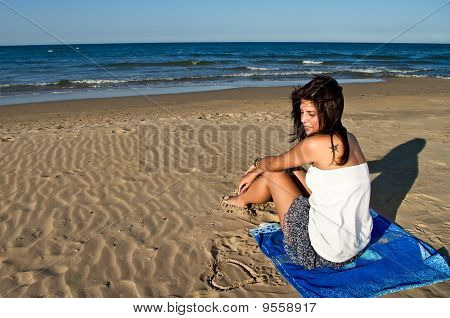 Girl with tattoo sitting by heart drawn in sand