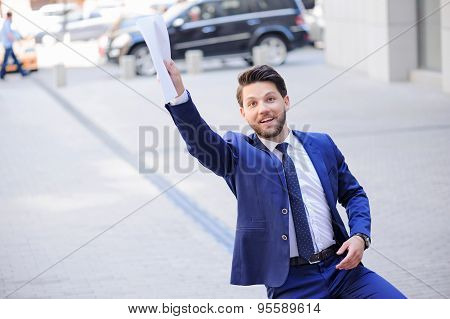 Positive businessman holding documents.