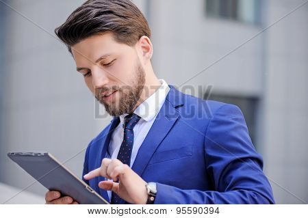 Nice positive bearded businessman holding laptop.