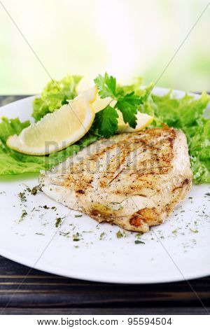 Dish of fish fillet with greens and lemon on bright background