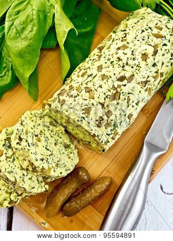 Butter with spinach and cucumbers on wooden board