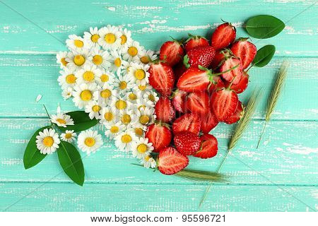Strawberry with chamomile, leaves and ears in shape of heart on color wooden background