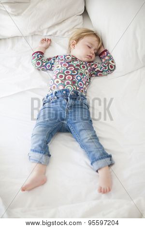 Jeans Baby Sleeping On White Bed
