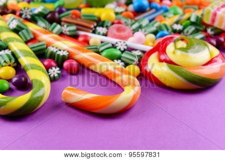 Colorful candies on purple background