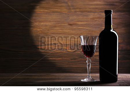 Wineglass and bottle on wooden background