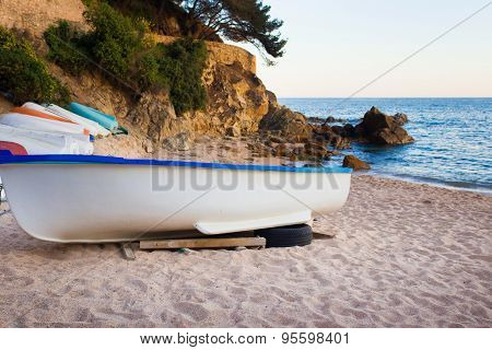 Old small boats on sandy beach. Weathered and dirty dinghies scattered across the sand
