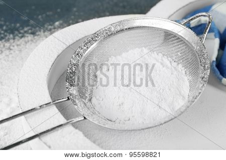 Sifting flour through sieve on wooden table, closeup
