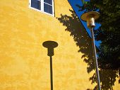 pic of lamp post  - Lamp Post Street Road Light Pole casting a shadow over a yellow house - JPG
