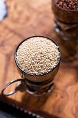 stock photo of quinoa  - White raw quinoa in a glass cup red quinoa on back olive wood background selective focus top view - JPG