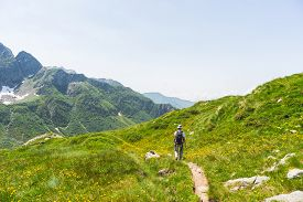 picture of italian alps  - One backpacker hiking uphill on footpath in the italian Alps - JPG