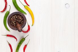stock photo of peppercorns  - Colorful chili peppers and peppercorn on white wooden table - JPG