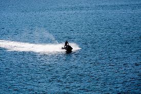 stock photo of waverunner  - Jet Ski Sillouette on Blue water of calm bay - JPG