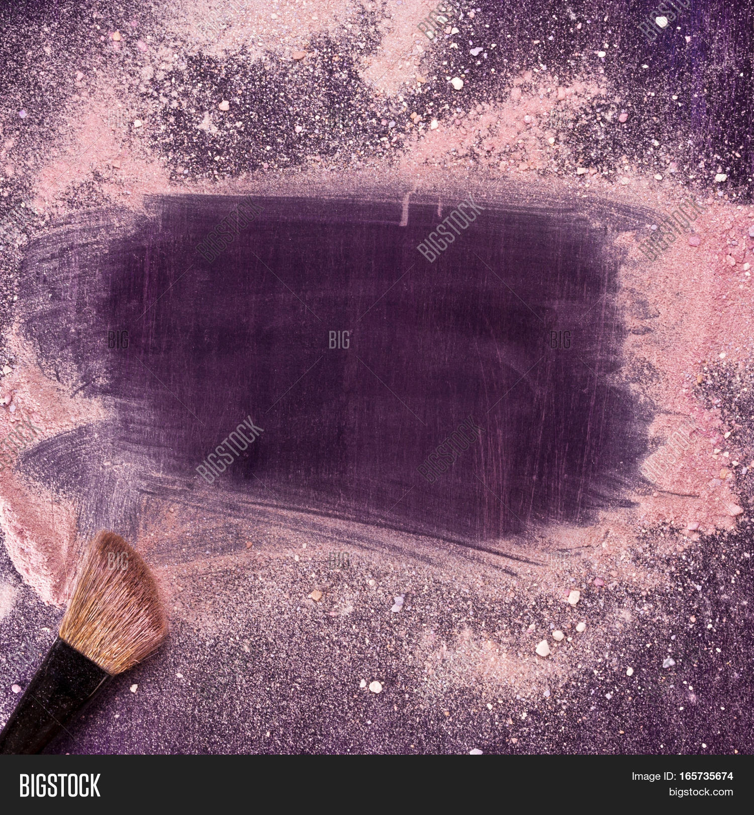 A makeup brush on a purple background, with traces of powder and ...