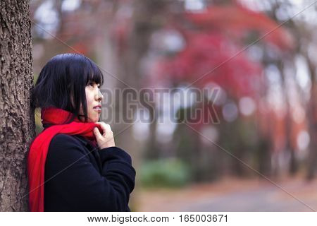 Portrait of a Japanese girl wearing a red scarf outdoors in a park during winter in Tokyo.