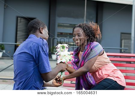 young man offering a flower to his wife to express his love for her.