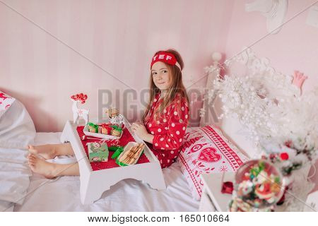 morning tea in bed dark-haired girl in red pajamas having breakfast