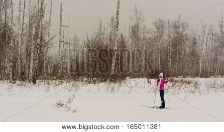 Tired girl standing on skis in winter forest