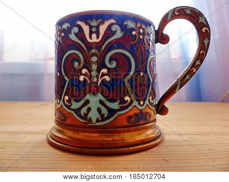 Cup holder. He appeared on the Russian railway in 1892. Coloured enamel, oriental pattern. Closeup. Retro.
