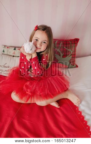 a large bed sits a girl in a red skirt and jacket with a white rabbit