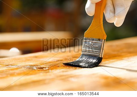 Gloved hand holding a paintbrush over wooden surface protecting wood for exterior influences and weathering. Carpentry wood treatment hard at work home improvement do-it-yourself concept.