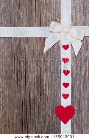Red hearts on old wooden background .