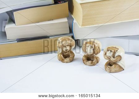 Three statuettes of monkey with many books as background