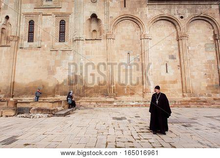 MTSKHETA, GEORGIA - OCT 14, 2016: Christian priest standing near the ornamental stone wall of Svetitskhoveli Cathedral built in 4th century on October 14, 2016. UNESCO World Heritage Site.