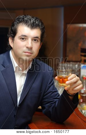 Young Man In A Bar With A Glass Of Whiskey