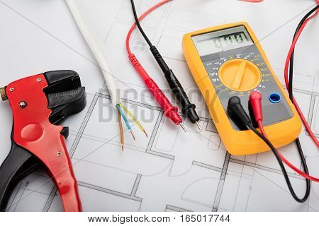 High Angle View Of Digital Multimeter On Blueprint With Red And Black Wire