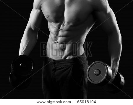 The top shape. Cropped monochrome shot of a fitness man exercising with dumbbells