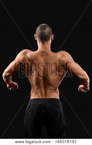 Back work. Male bodybuilder showing off his toned muscular back posing on dark background