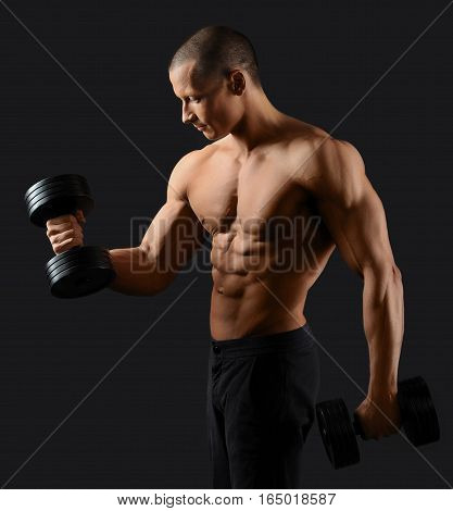 Ironman. Young handsome bodybuilder showing off his sexy ripped body working out with weights
