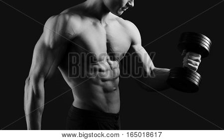 Muscle definition. Cropped monochrome shot of a male bodybuilder working out shirtless showing off his hot ripped muscular body